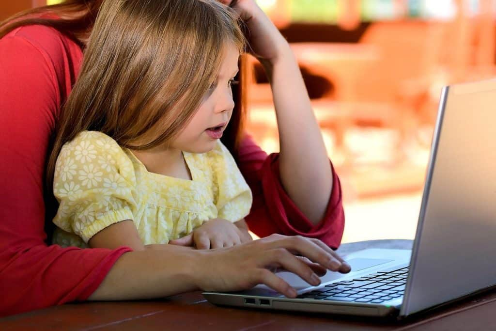child with adult on laptop