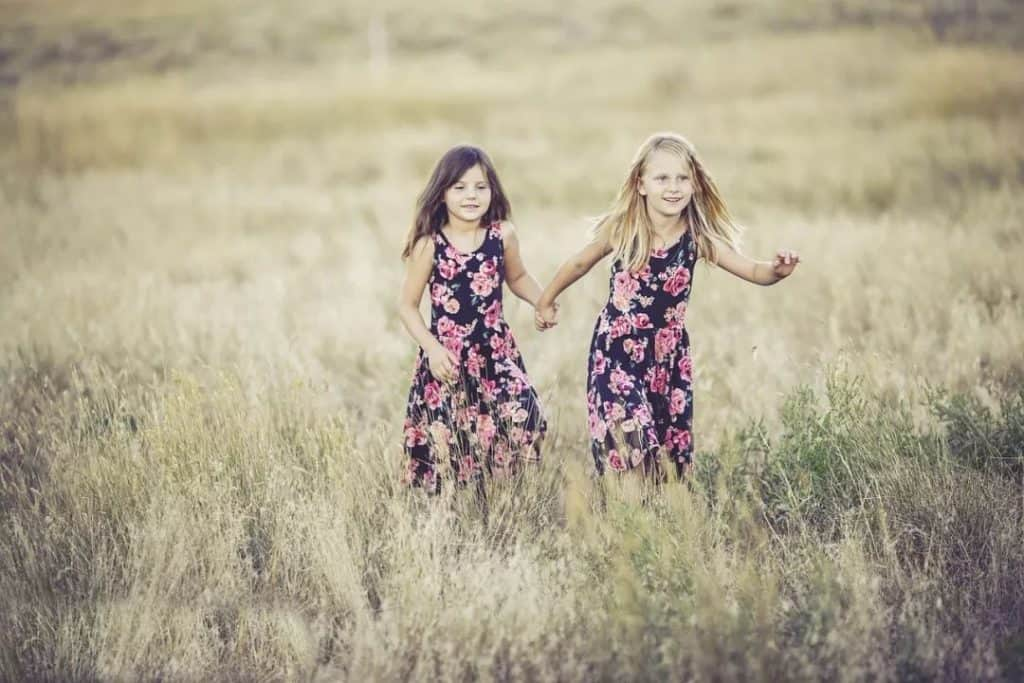 young girls holding hands and running in a field