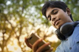 Happy teenager boy using mobile phone and headphones in natural background.