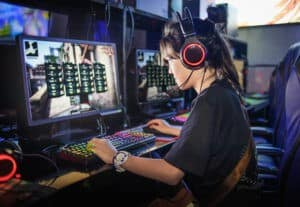 Young person using a computer with headphones.