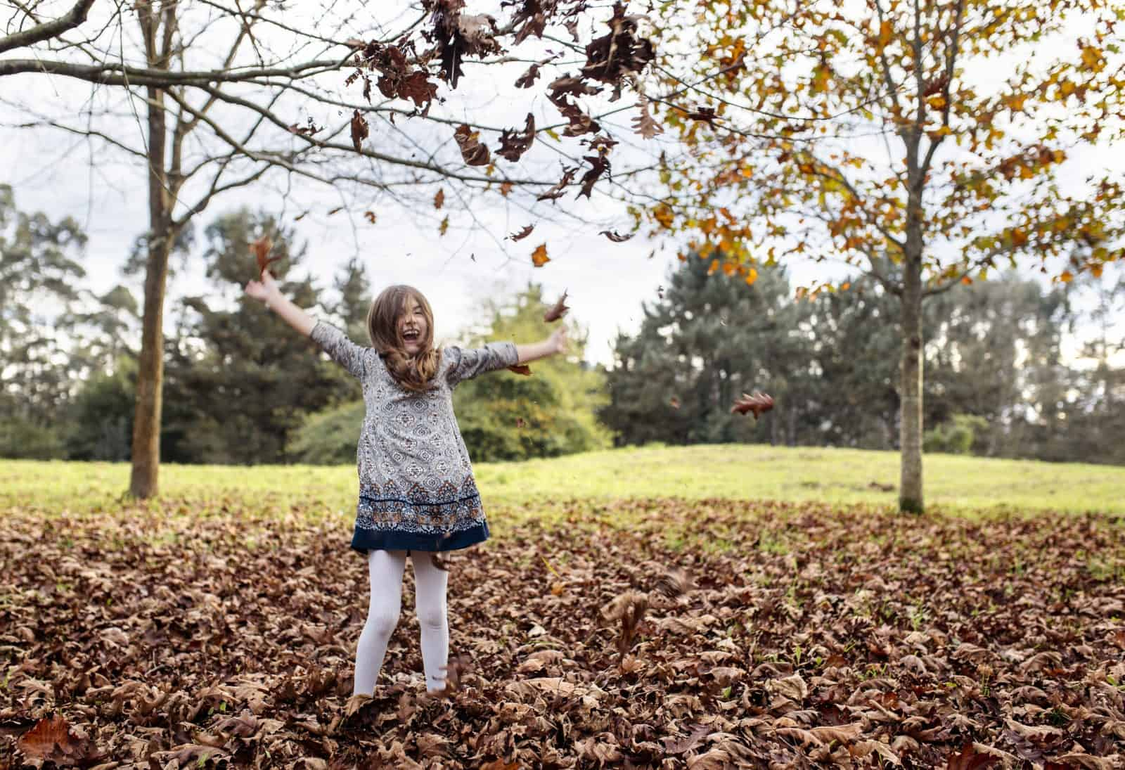 Laughing girl throwing autumn leaves in the air