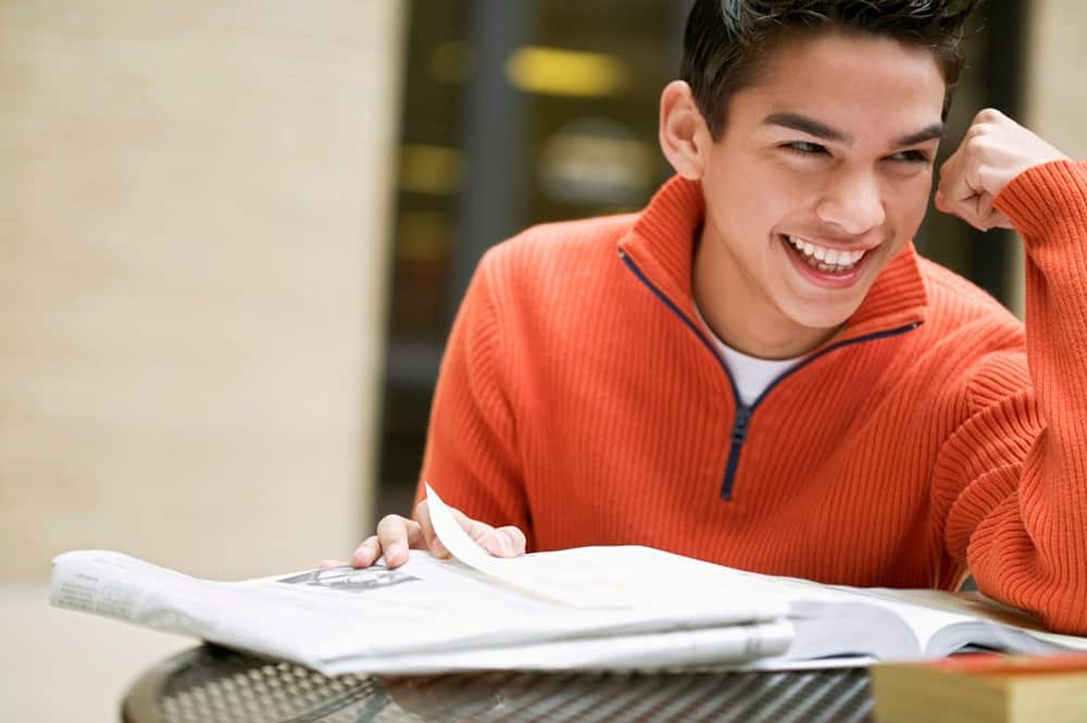 young man smiling with book