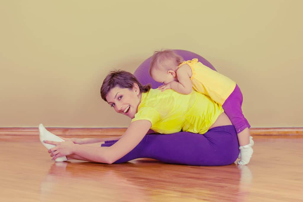 woman exercising with child