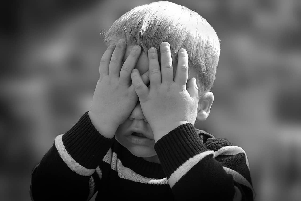 child hiding behind hands