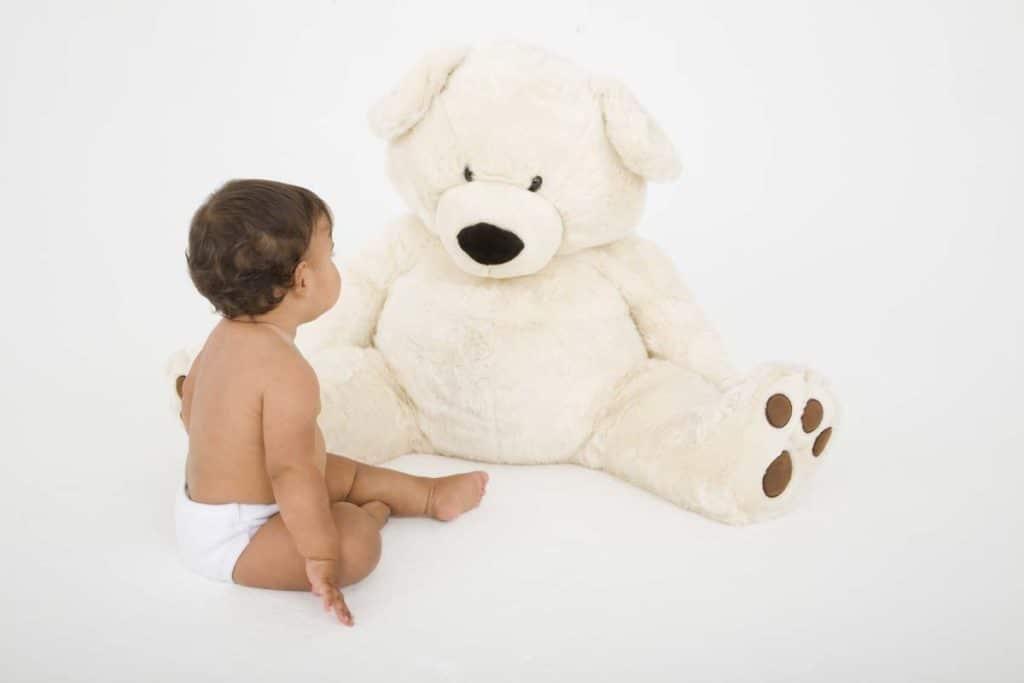 Baby sitting with teddy bear