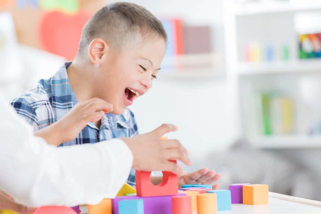 Cheerful preschool age boy enjoys playing with blocks with his teacher. Only the teachers arms are seen in the photo.