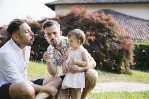 Gay couple playing with their child in the garden