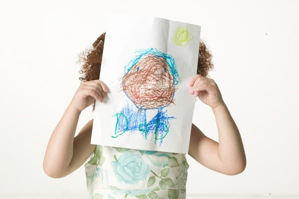 child holding paper over face