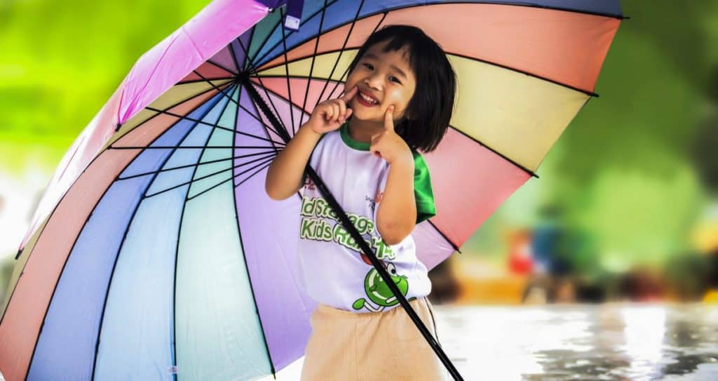 asian girl holding umbrella and smiling