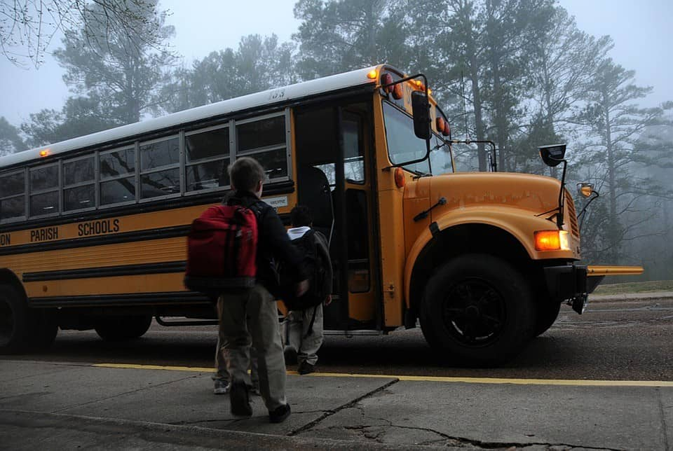 children getting on school bu