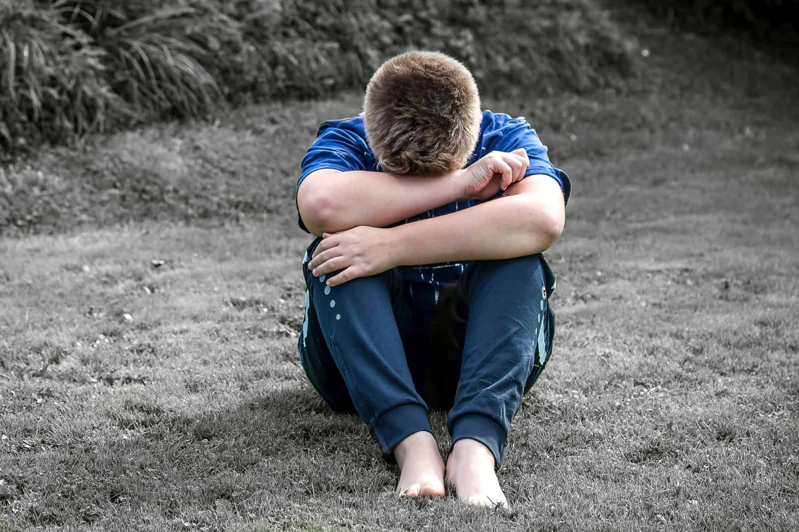 boy crying on ground