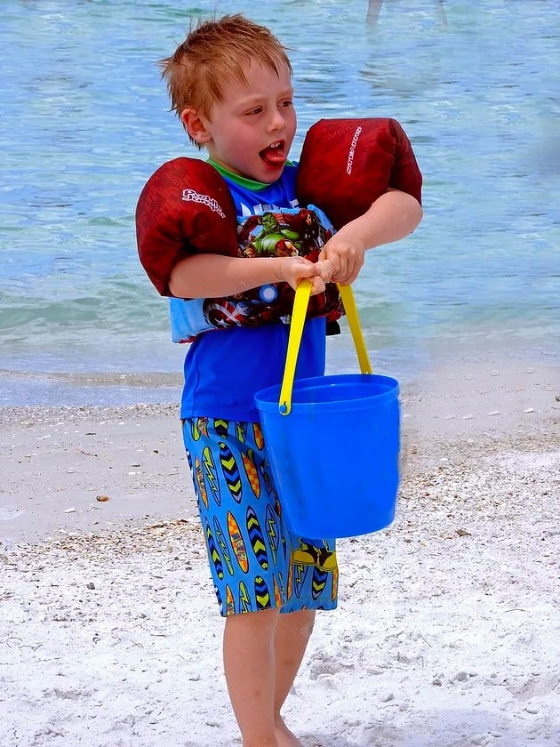 child carrying bucket at beach
