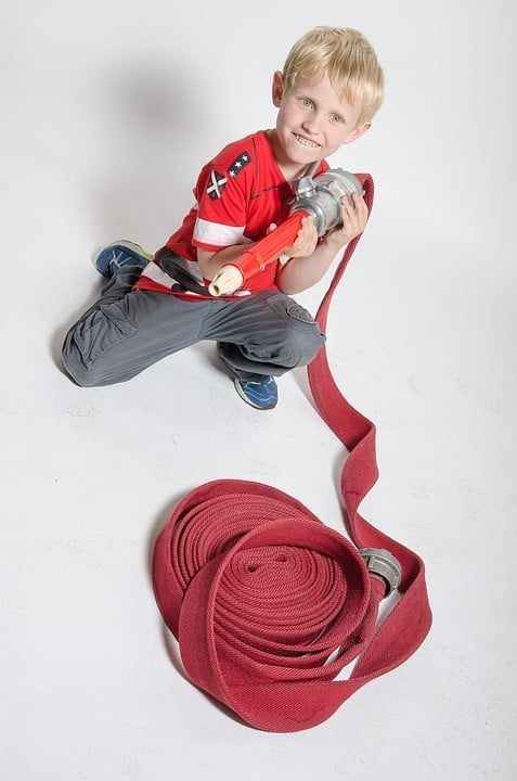 child playing with fire hose
