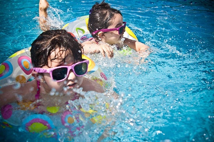 children swimming with blow up rings