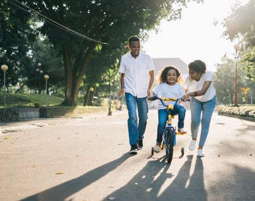 mom dad and child on bicycle