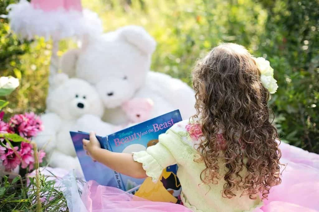 girl reading book to stuffed animals