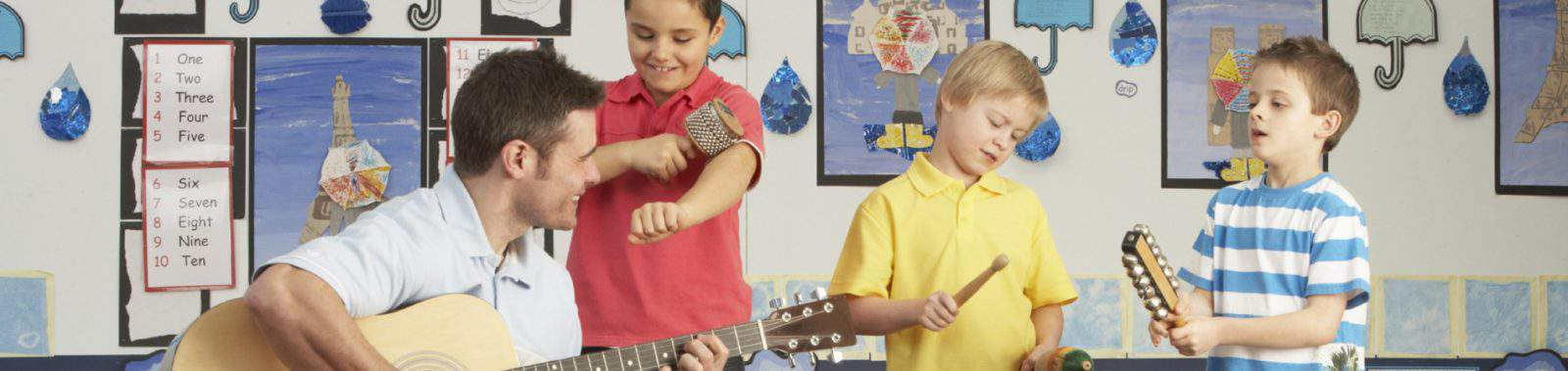 Male Teacher Playing Guitar With Pupils Having Music Lesson In Classroom