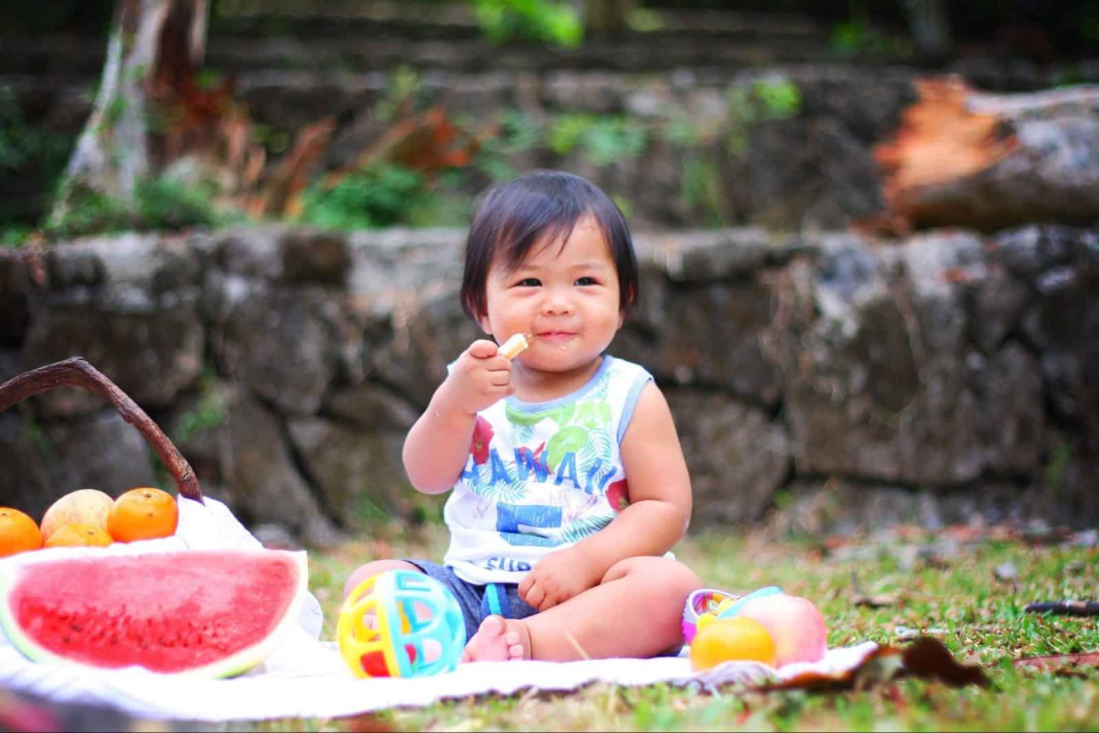 toddler eating on blanket