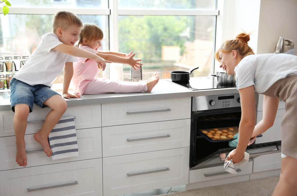 Young mother and kids tasting biscuits in kitchen