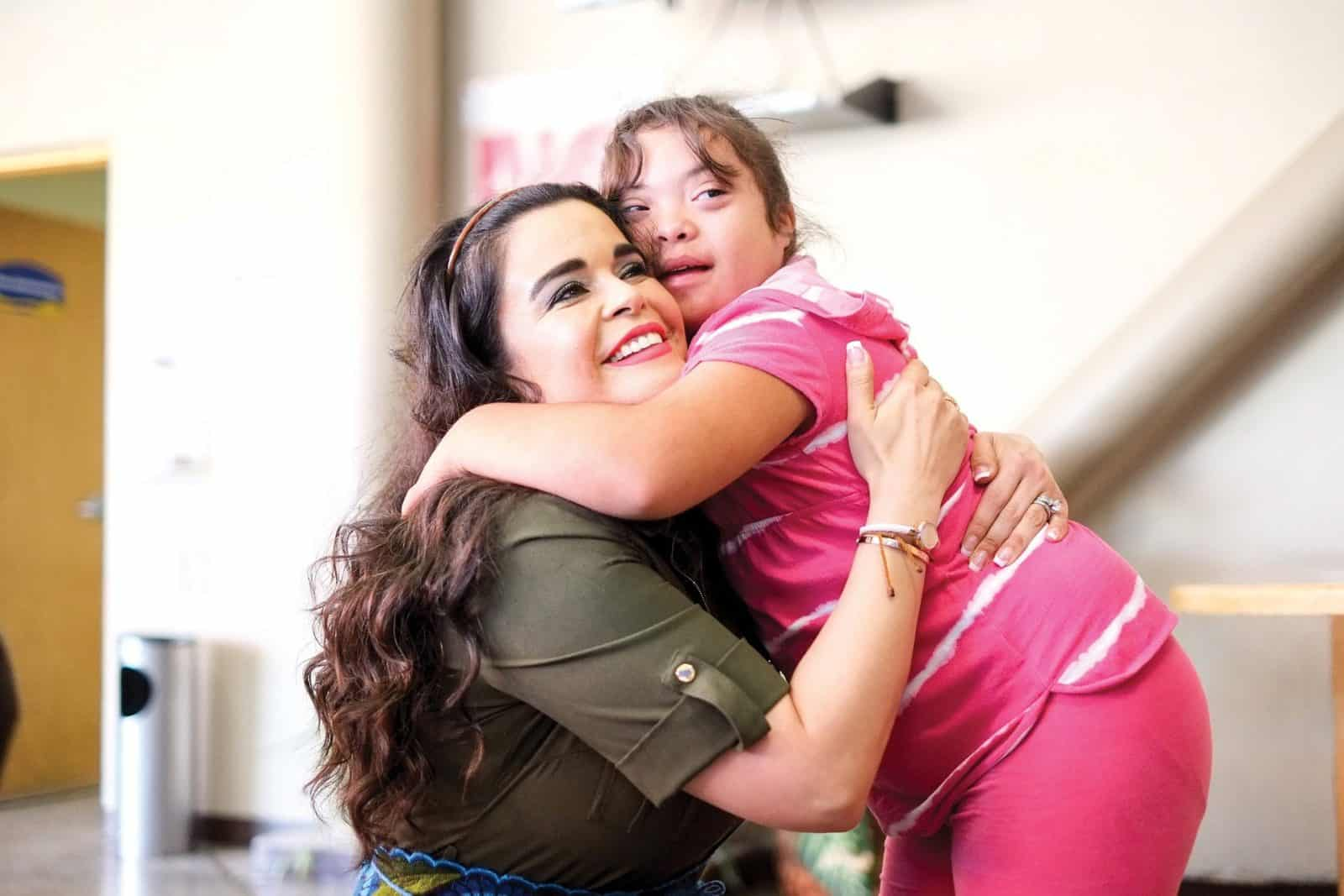 woman hugging child with downs syndrome