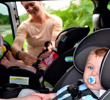 woman placing children in car seats