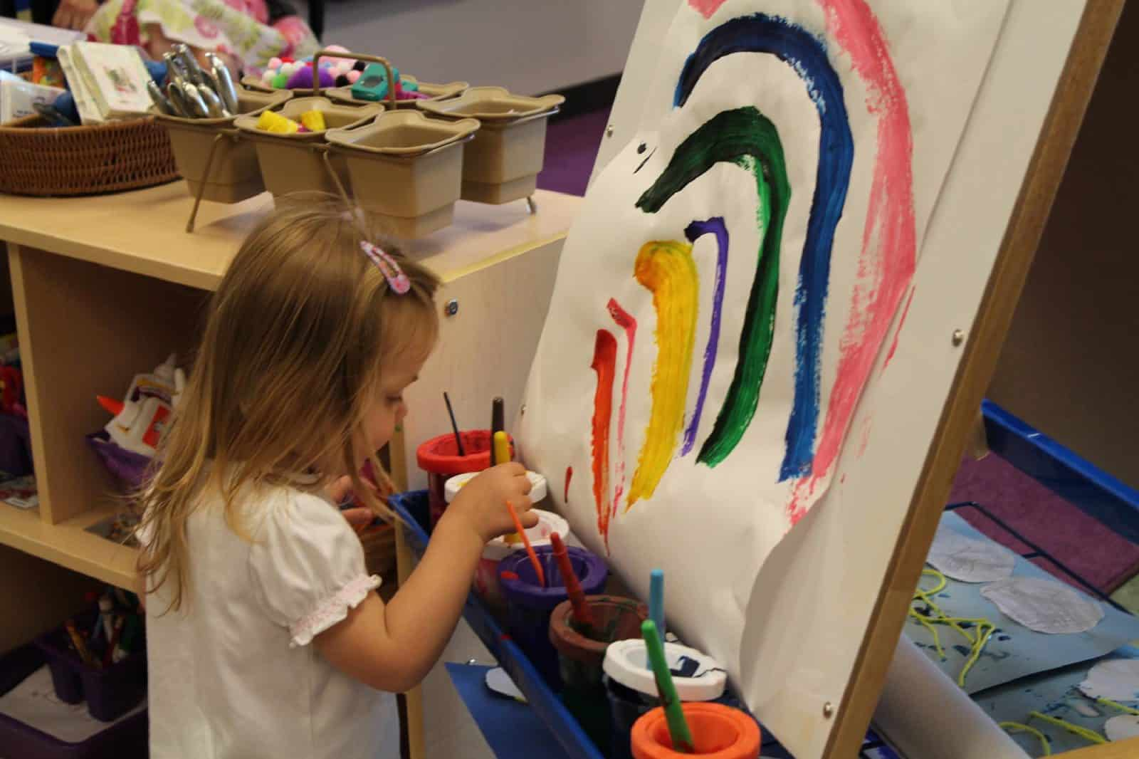 young girl painting rainbow on paper