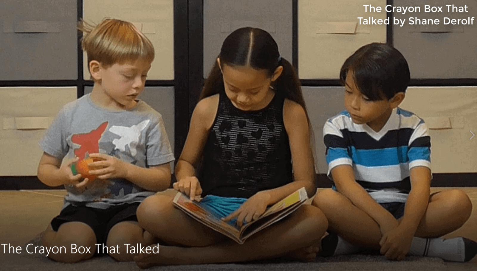 girl reading book to boys